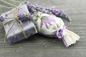 lavender soap and scented sachets with fresh flowers over wooden background